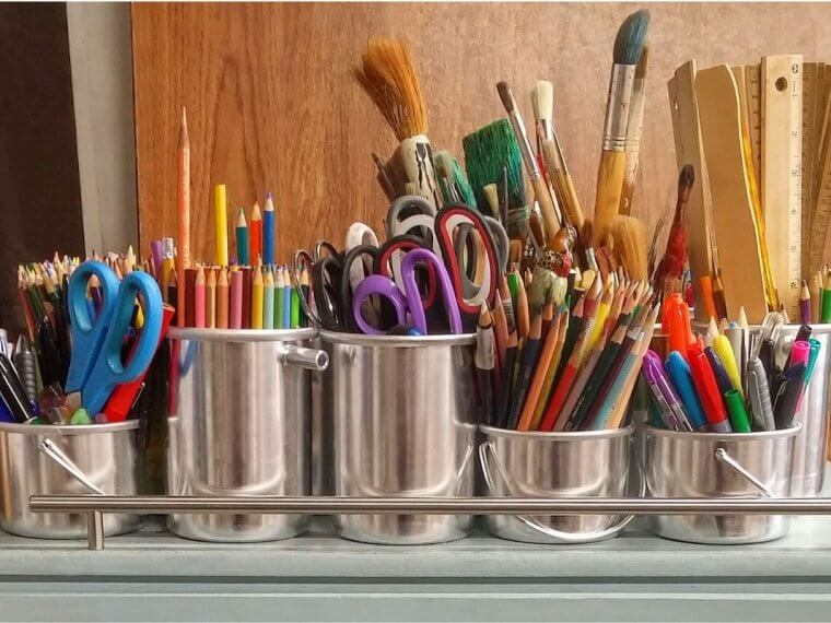 Silver pots full of paint brushes and pens