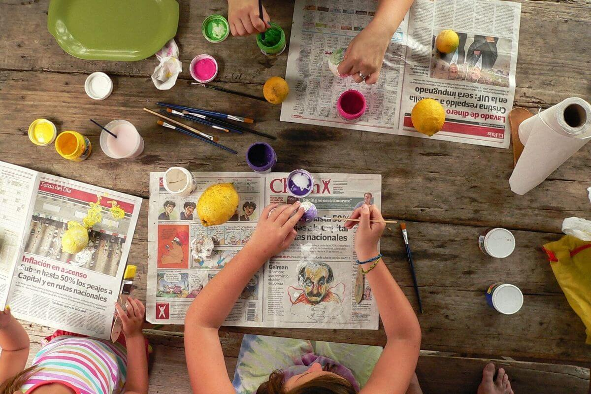 Children doing craft on a newspaper outside