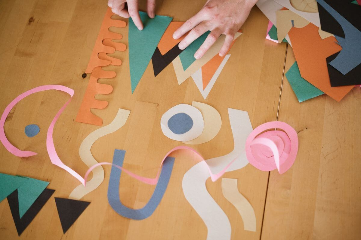Someone cutting up paper into different shapes
