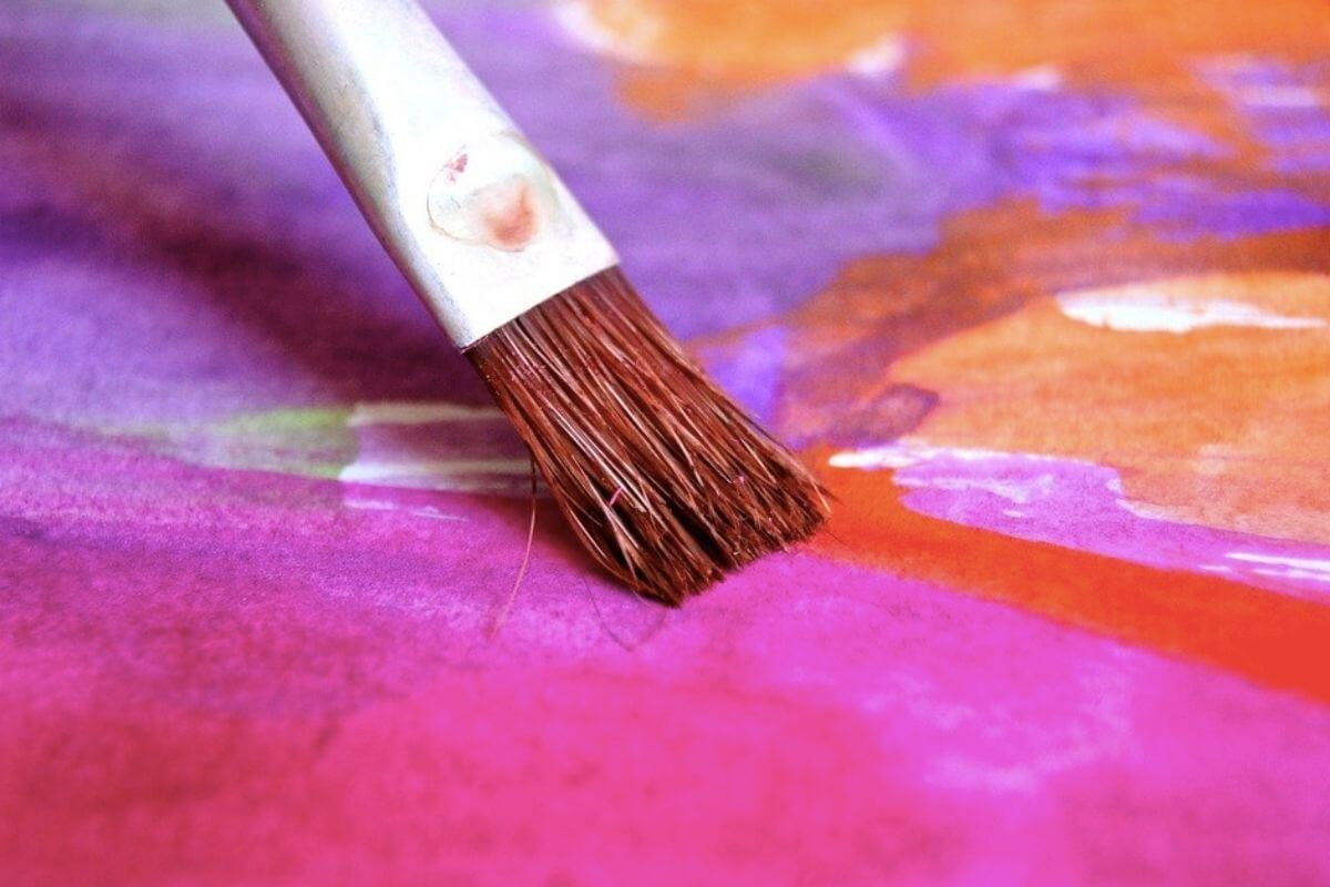 Paint brush with purple, pink and orange water colour