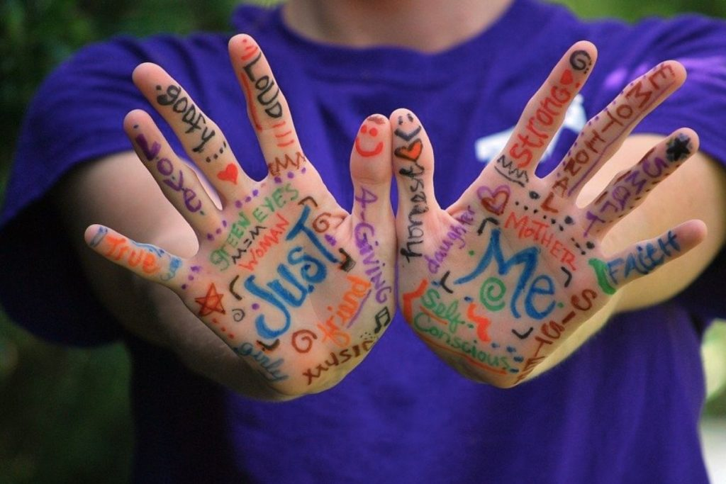 A child holding their hands with paint on
